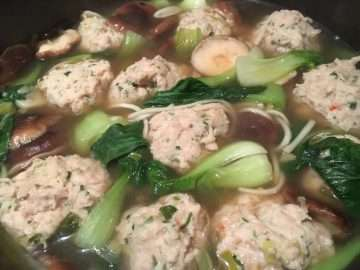 Chicken dumplings poached in fragrant broth with shitake and pak choy